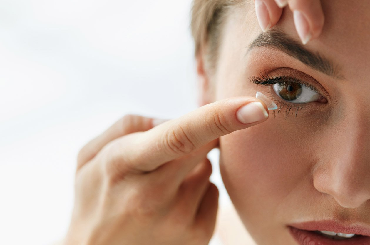 A woman putting in Acuvue Oasys Transition Contact Lenses